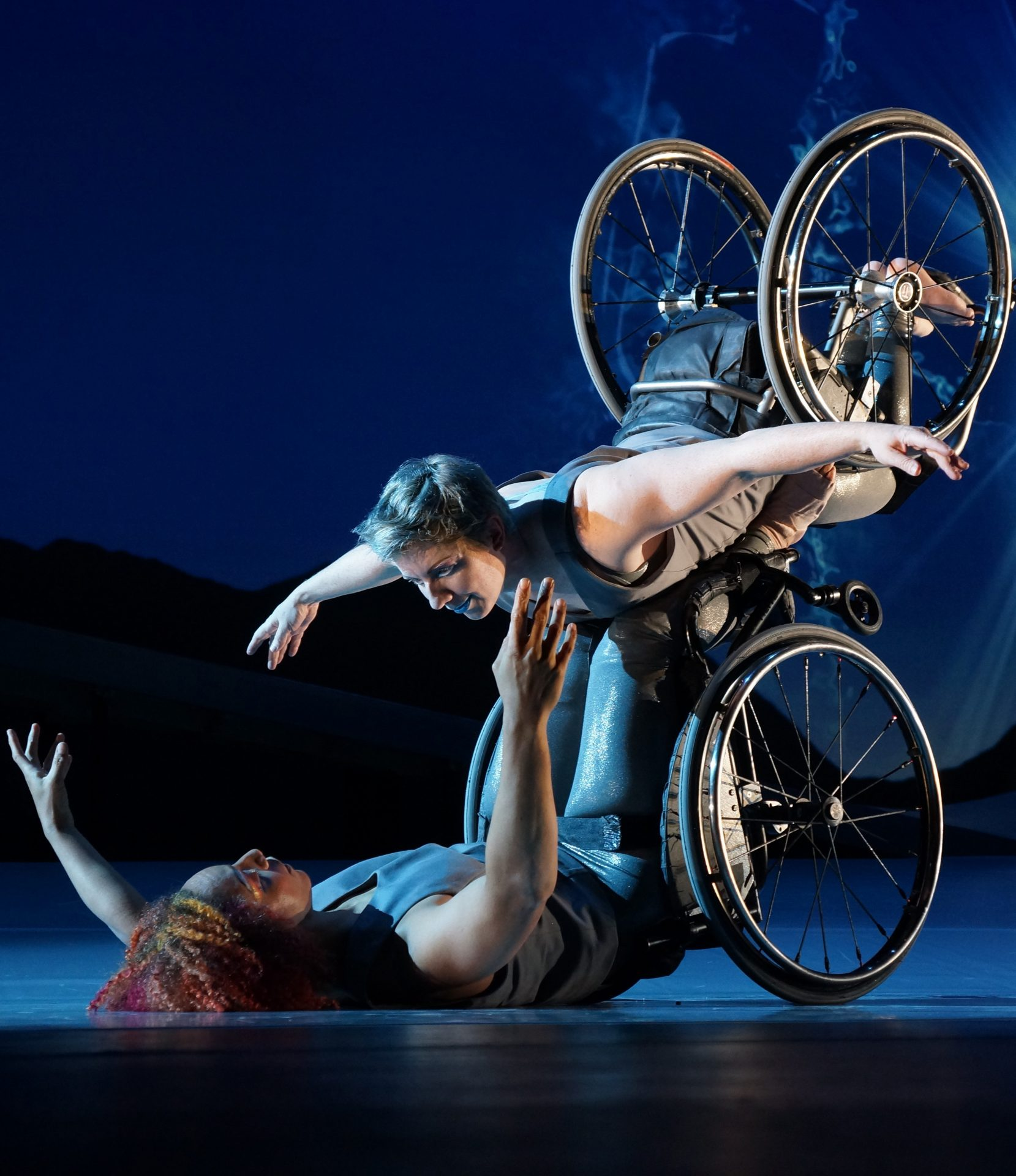 Kinetic Light DESCENT. Dancer Laurel Lawson as Venus is flying in the air with arms spread wide, wheels spinning, and supported by dancer Alice Sheppard as Andromeda who is lifting from the ground below. They are making eye contact and smiling. Photo by Jay Newman / BRITT Festival.